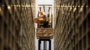 Photograph of worker between two enormously high stacked bookshelves at the Harvard Depository