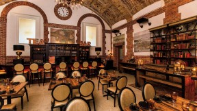 Cozy Map Room Tea Lounge with books, bar, and vaulted ceiling