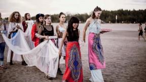 A procession of women heading toward a lake