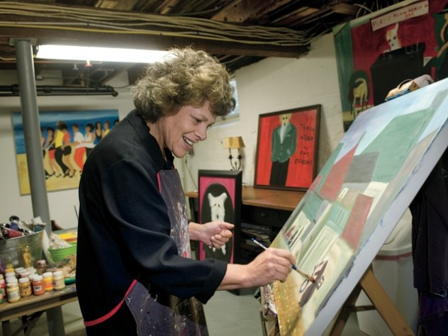 Surrounded by her own works, Langer wields a brush in her home studio.  A self-taught painter who took up the avocation in midlife, she describes her autodidactic approach to art in <em>On Becoming an Artist: Reinventing Yourself Through Mindful Creativity</em> (2005).
