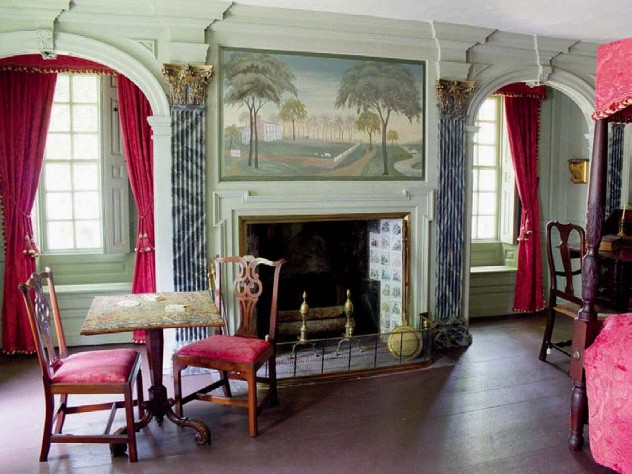 A grand bedroom with four-poster bed and elegant fireplace in the main house.