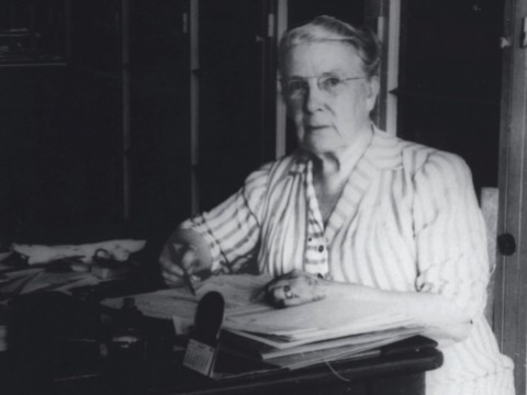 Photograph of a stout middle-aged woman seated at her desk, writing