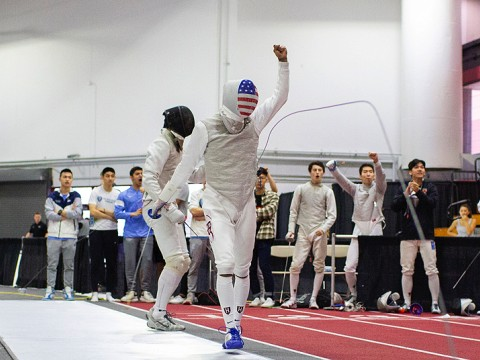 A fencer walks away from his opponent, holding up a fist