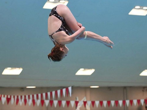 Georgina Milne flies through the air, flipping toward the water.
