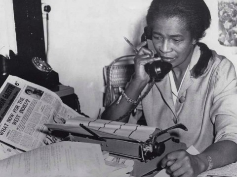 "Black journalist Claudia Jones on the phone in the offices of the ""West Indian Gazette"" in London"