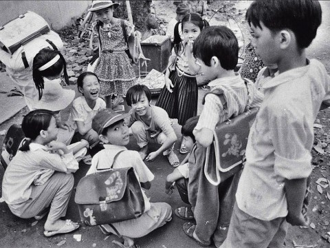"Black and white photo of a group of Vietnamese children, titled ""Schoolchildren Playing Cards"""